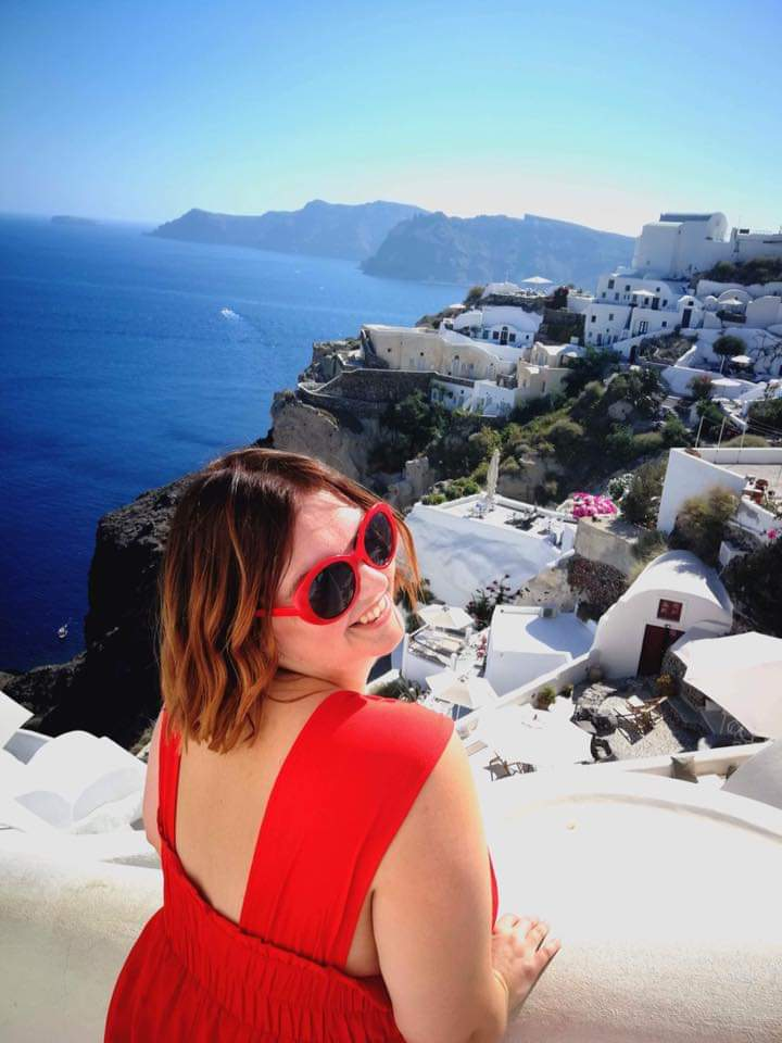 girl dressed in red jumpsuit and matching red glasses standing in front of the iconic blue domes in Greece, smiling at the camera